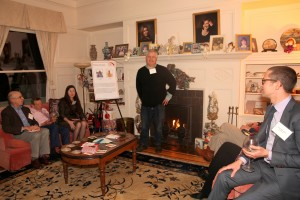 A man stands talking in front of a lit fireplace and mantel. People sit on couches of either side of him, some with plates of food and some holding glasses of wine.