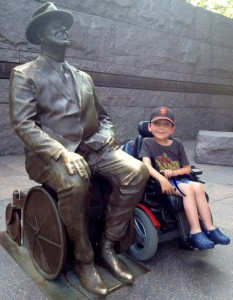 A young boy smiles in his wheelchair side by side with a slighty larger than life metal statue of President Franklin Delano Roosevelt also in his wheelchair.