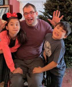 Sasha Blair-Goldensohn raises his splayed hands. His daughter, wearing Minnie Mouse ears, leans on the right side of his wheelchair, and his son leans on the left. The three are making silly faces for the camera.