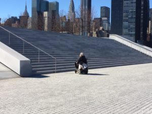 A woman using a power chair is at the base of a granite stairway in a park.