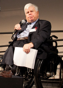 Light-skinned man with white hair holding a microphone and papers in his wheelchair on a stage.
