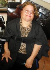 Olive-skinned woman with glasses and a leopard-print scarf on her hair smiling in her powerchair.