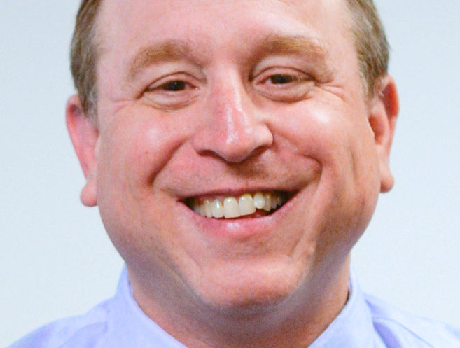 Portrait-style photo of Larry Paradis. He is smiling in a collared shirt and tie.