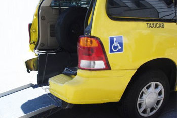 Rear of a yellow taxi van with its trunk door open and a wheelchair tamp