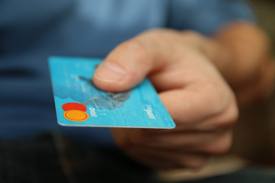 A person's hand holding a credit card.