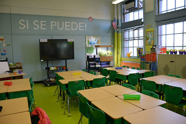 A classroom with desks arranged in clusters. The wall says