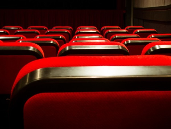Rows of red movie theater seats, seen from behind.