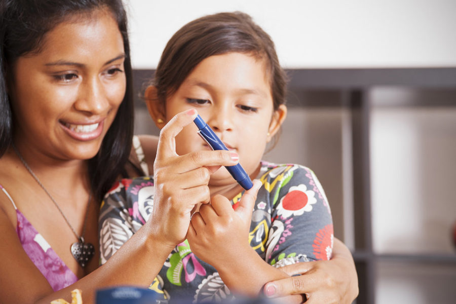 A smiling woman has her arm around a child. The woman is holding a insulin pen to the child's thumb.