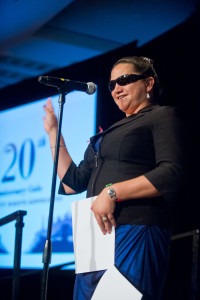 Lisamaria stands smiling in front of a microphone with her right hand raised and her left hand reading and pressing a braille sheet against her hips.