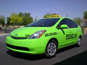 Photo of a vehicle in Discount Cab's fleet, a bright green Toyota Prius