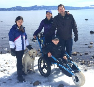 Steve Ragland, his wife, and two children are all on a snowy rocky shore in winter garb, with water and mountains behind them. His daughter stands by their yellow labrador and his son sits in a wheelchair built for rugged terrain.