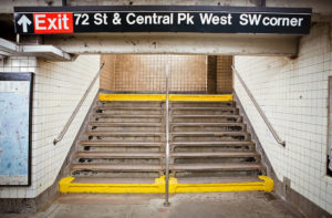 "Concrete stairs inside a subway station, flanked by metal handrails and tiled walls. A sign above says ""Exit, 72 Street & Central Park West, SW corner."""