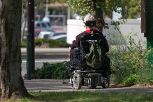 A person in a powerchair travels down a sidewalk