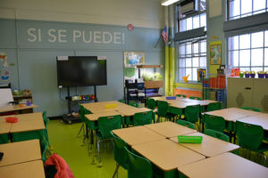 "A classroom with desks arranged in clusters. The wall says ""SI SE PUEDE!"""