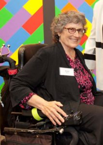Light-skinned woman with brown hair and glasses smiling in her powerchair.