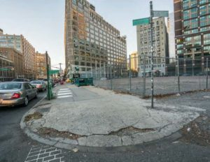 A curb cut on a street corner in NYC. The surface is missing big chunks of cement, making it very hazardous.