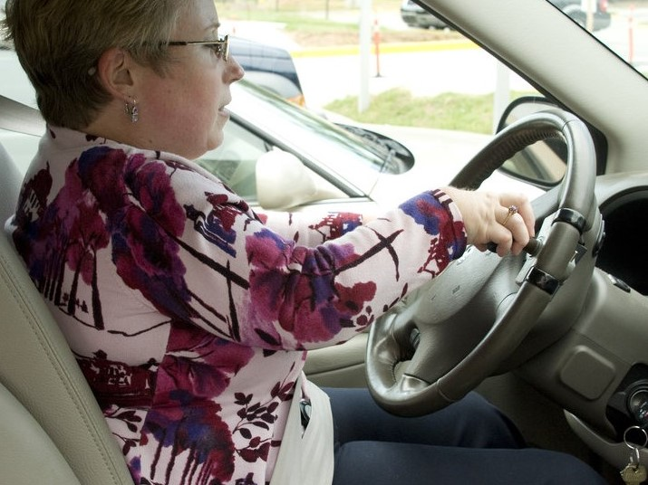 The woman pictured here, had just boarded her vehicle by way of an access ramp, while seated in her wheelchair, and had maneuvered herself into the driver's-side swivel seat. Due to her disability, the steering wheel was equipped with a hand control, which she held in her right hand, enabling her to operate the accelerator and braking system using her hand rather than her feet.