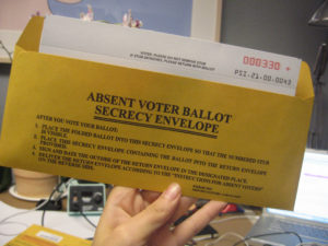 """An envelope being held up """"Absent Voter Ballot Secrecy Envelope"""" with instructions"""