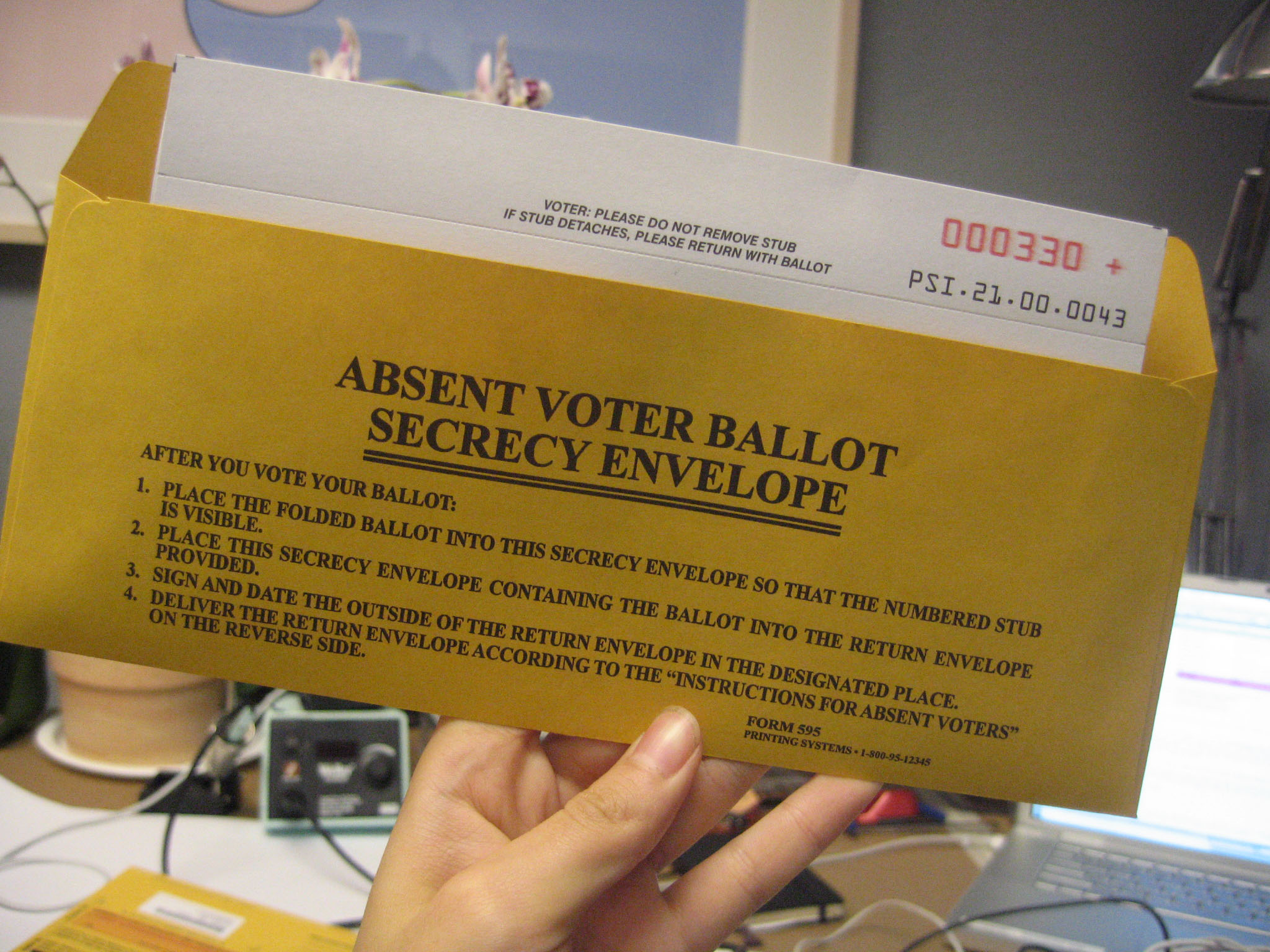 "An envelope being held up ""Absent Voter Ballot Secrecy Envelope"" with instructions"