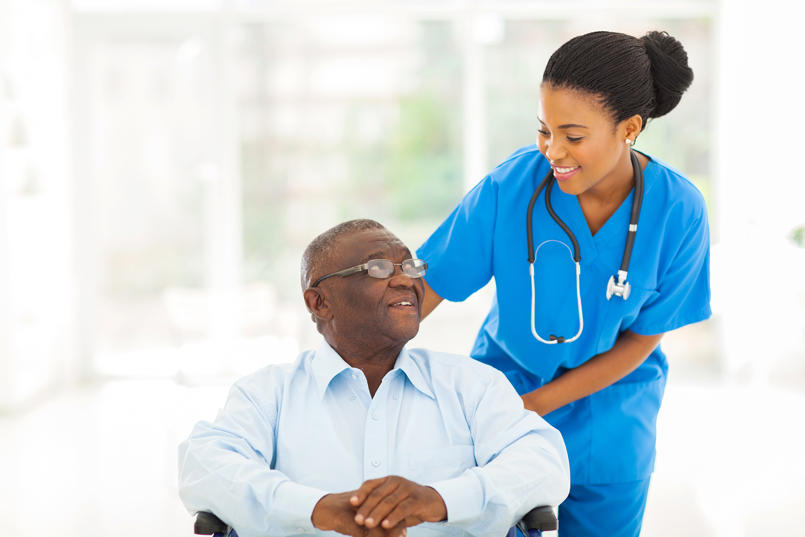 Nurse speaking with senior patient in wheelchair