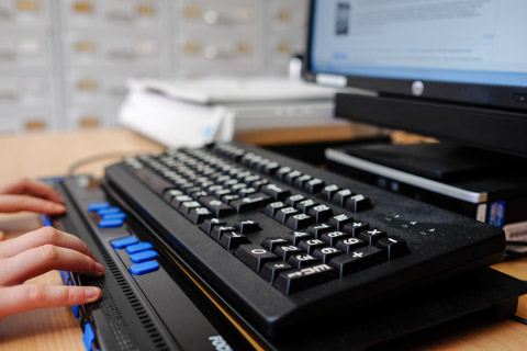 Close up of a person's hands using a braille keyboard to read information on a computer monitor, in an office setting