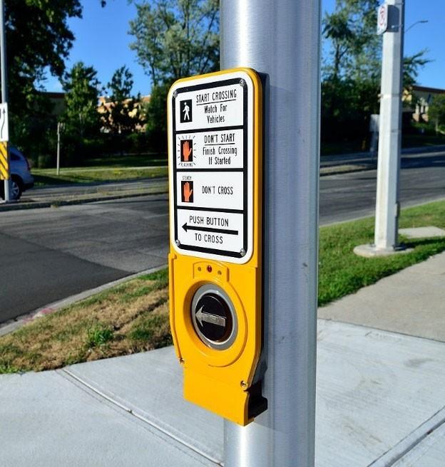 Yellow accessible pedestrian signal on a pole on a sidewalk