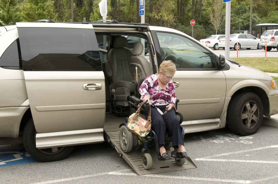 Woman in wheelchair moving backwards up the ramp of a wheelchair-accessible van parked in a parking lot