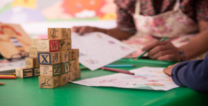 Hands of a woman and child using colored pencils to draw on paper on a desk with building blocks and other art supplies