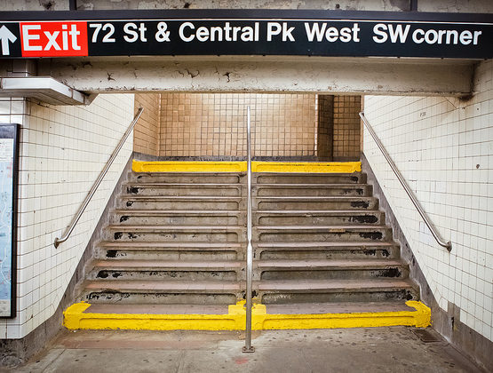 Concrete stairs inside a subway station, flanked by metal handrails and tiled walls. A sign above says
