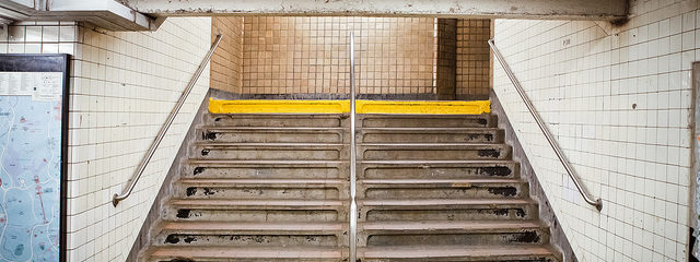 Concrete stairs inside a subway station, flanked by metal handrails and tiled walls. A sign above says \