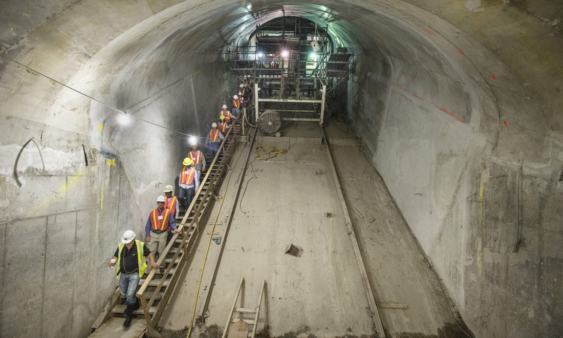 Construction workers in a long, sloped NY subway station