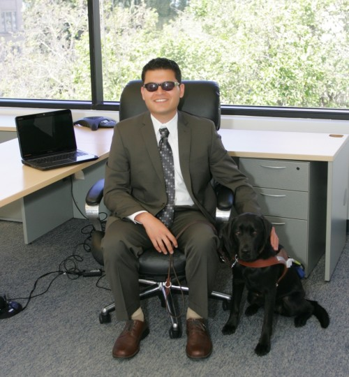 Mike Nuñez seated at his desk with guide dog Peggy.