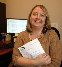 Anne Kelsey sits holding a packet of paper, smiling, with her computer screen behind her shoulder