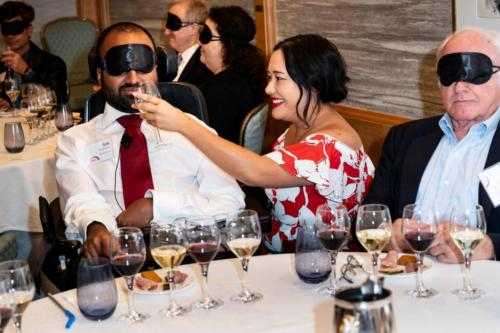 Guests participate in the blindfolded wine tasting.