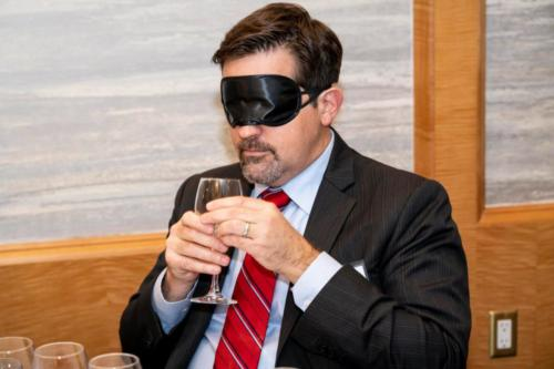 Board member Steven Ragland participates in the blindfolded wine tasting.