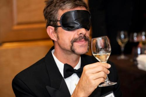 A man participates in the blindfolded wine tasting.