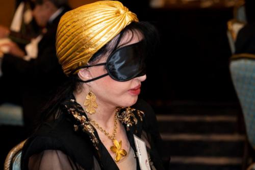 A woman participates in the blindfolded wine tasting.